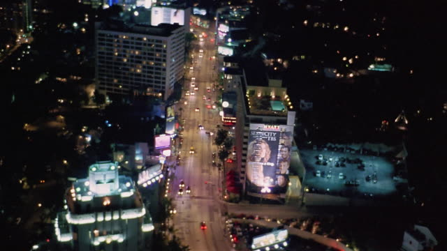 vídeos de stock e filmes b-roll de aerial view of traffic and buildings along sunset boulevard at night / los angeles - bulevar