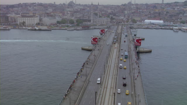 aerial view of traffic crossing the galata bridge over the golden horn harbor in the strait of bosphorus in istanbul. - golden horn istanbul stock videos and b-roll footage