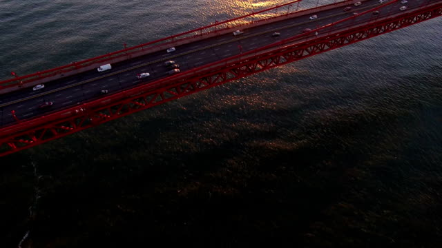 aerial view of traffic moving on golden gate bridge with sunlight at sunset - golden gate bridge stock videos & royalty-free footage