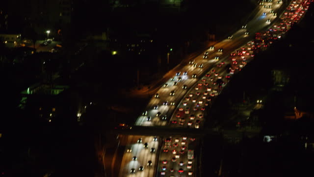 ws aerial view of traffic moving on highway in city at night - dividing line stock videos & royalty-free footage
