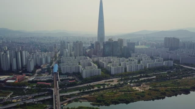 aerial view of traffic of car driving on bridge cross over han river into lotte world tower in seoul city, south korea - south korea stock videos & royalty-free footage