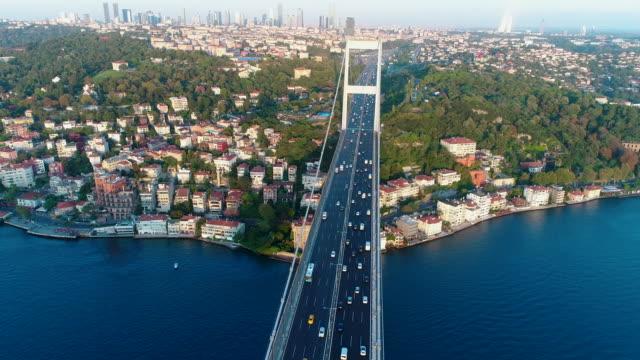 aerial view of traffic on bridge 4k- drone shots of fatih sultan mehmet bridge on istanbul bosphorus at sunrise - built structure stock videos & royalty-free footage