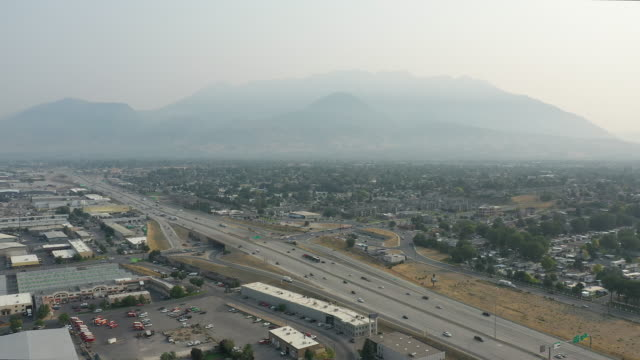 vídeos de stock e filmes b-roll de aerial view of traffic on i-15 in utah county with smokey skies - orem