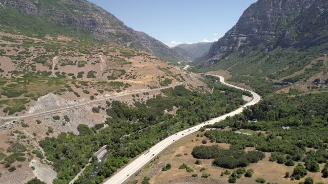 vídeos de stock e filmes b-roll de aerial view of traffic on windy road through canyon - provo