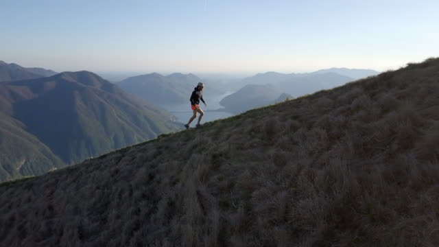 Aerial view of trail runner ascending ridge above alps and lake