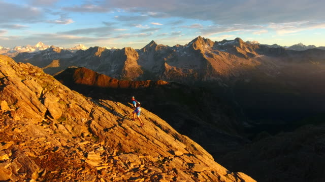Aerial view of trail runner ascending rocky mountain at sunrise