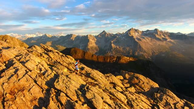 Luftaufnahme des Trailläufer aufsteigender felsigen Berg bei Sonnenaufgang