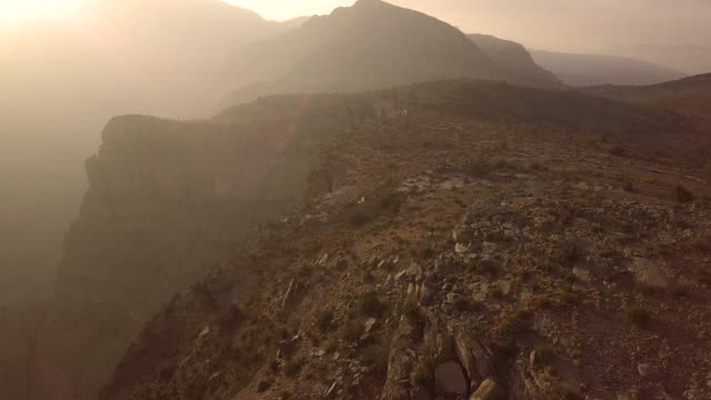 aerial view of trail runner ascending rocky trail above canyon at sunrise - canyon stock videos & royalty-free footage