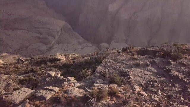vídeos y material grabado en eventos de stock de aerial view of trail runner ascending rocky trail above canyon at sunrise - omán