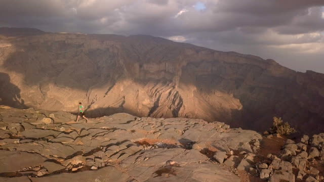 aerial view of trail runner ascending rocky trail above canyon at sunrise - cross country running stock videos & royalty-free footage