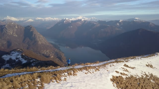 Aerial view of trail runner descending mountain ridge above lake and snow-capped mountains