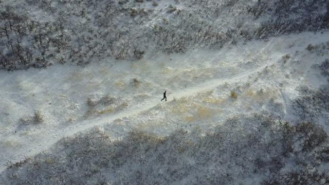 vidéos et rushes de vue aérienne du coureur de trail sur neige - voie piétonne