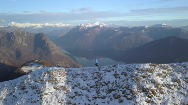 aerial view of trail running descending mountain ridge to take selfie above lake and snow-capped mountains - cross country running stock videos and b-roll footage