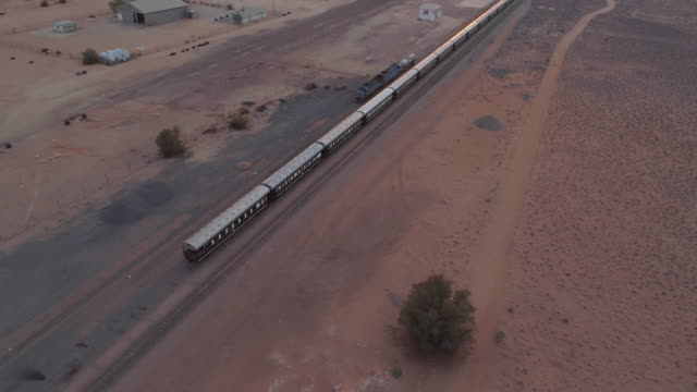 aerial view of train on desert during sunset, drone moving over landscape - swakopmund, namibia - stationary stock-videos und b-roll-filmmaterial