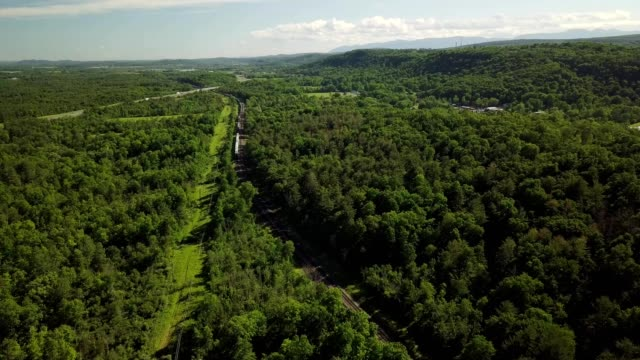 aerial view of train tracks cutting through forest in blandford massachusetts - massachusetts stock videos & royalty-free footage