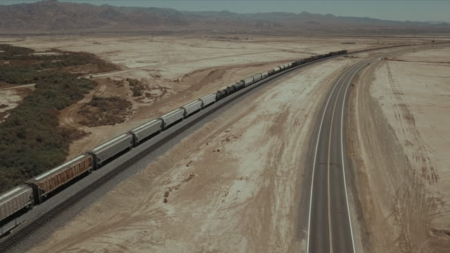 aerial view of train tracks in the desert. - tramway stock-videos und b-roll-filmmaterial