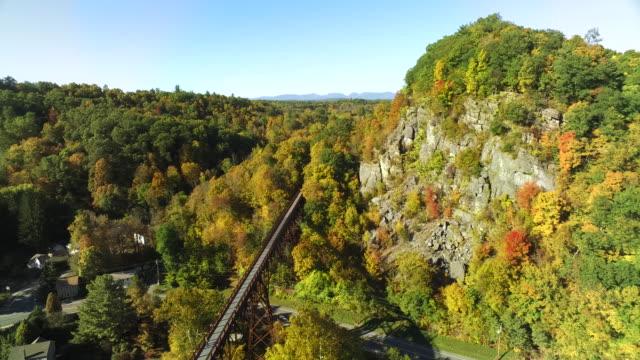 aerial view of train trestle disappearing into beautiful fall foliage - ニューパルツ点の映像素材/bロール
