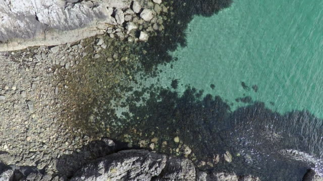 Aerial view of transparent water and stone beach in Kerrera island, Scotland