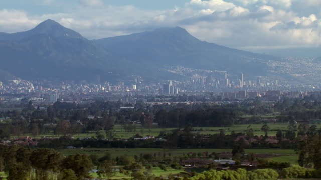 aerial view of tree covered landscape with city and mountains in background, bogota, colombia - bogota stock videos & royalty-free footage
