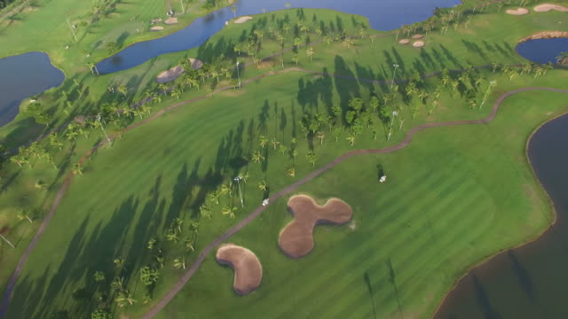 aerial view of tree lined golf course - golf course stock videos and b-roll footage