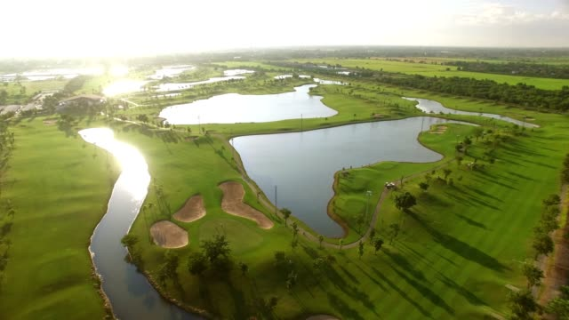 aerial view of tree lined golf course - golf stock videos & royalty-free footage