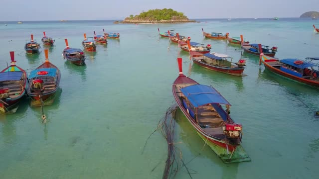 vídeos de stock e filmes b-roll de aerial view of tropical beach, long tail boat and rocky coast with crystal clear turquoise water on thai island, sunrise beach, koh lipe, satun, thailand - indústria pesqueira