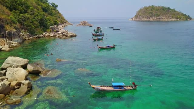 aerial view of tropical beach, long tail boat, kayak and rocky coast with crystal clear turquoise water koh lipe, satun, thailand - pattaya stock videos & royalty-free footage