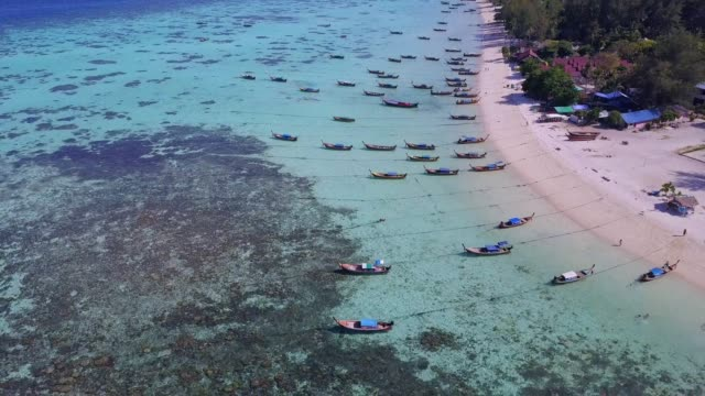 aerial view of tropical beach, long tail boat, kayak and rocky coast with crystal clear turquoise water koh kla, koh lipe, satun, thailand - pattaya stock videos & royalty-free footage