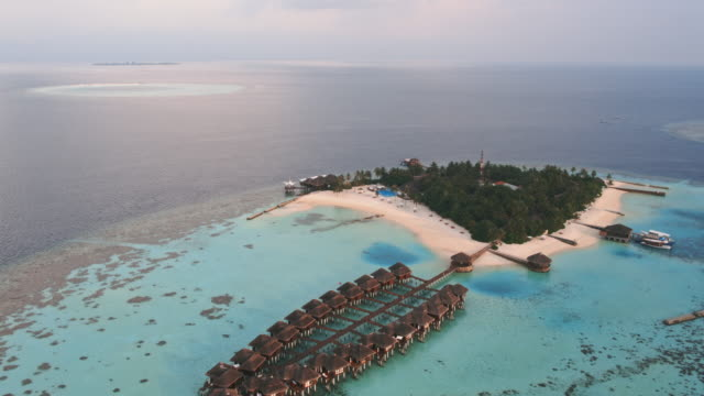 aerial view of tropical island at sunset, maldives - orizzonte sull'acqua video stock e b–roll