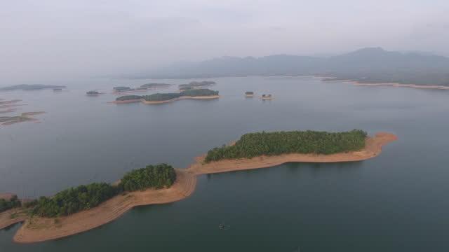 vídeos de stock e filmes b-roll de aerial view of tropical island in lake among - árvore tropical