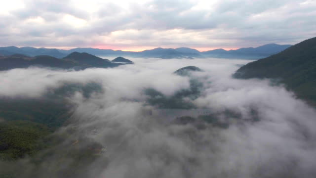 aerial view of tropical mountain range and lake with fog - mountain range stock videos & royalty-free footage