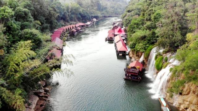 vídeos de stock e filmes b-roll de aerial view of tropical village with waterfall in national park at kanchanaburi - empreendimento turístico