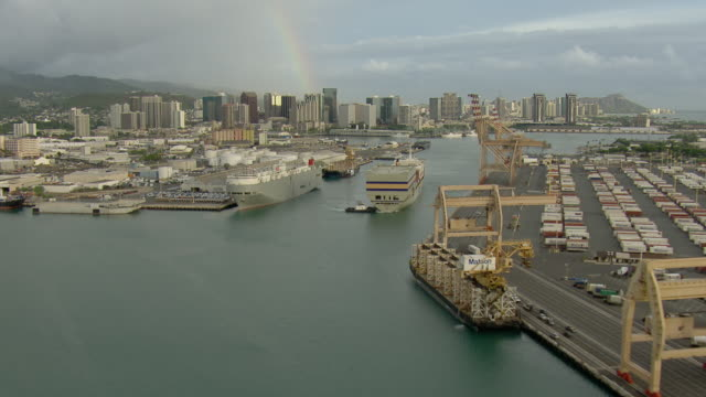 aerial view of tugboat and container ship with honolulu skyscrapers and rainbow. - oahu stock videos and b-roll footage