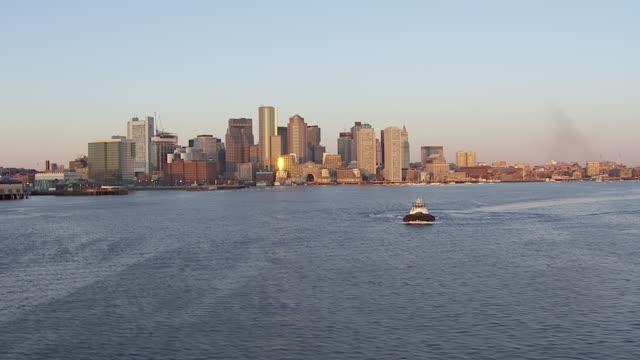aerial view of tugboat moving in harbor with boston skyline in background, massachusetts, united states of america - custom house tower stock videos & royalty-free footage