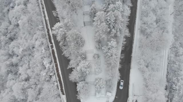 luftaufnahme des drehen straße im winter tief verschneiten bergwald - aircraft point of view stock-videos und b-roll-filmmaterial