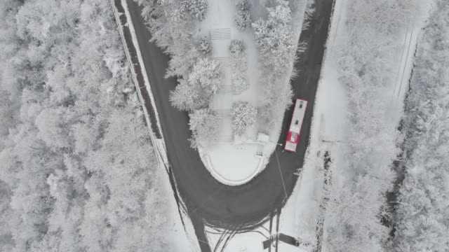 aerial view of turn road in mountain winter snow covered forest - bus stock videos & royalty-free footage