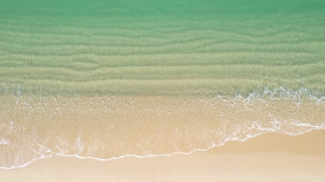 aerial view of turquoise ocean wave reaching the coastline - on top of stock videos & royalty-free footage