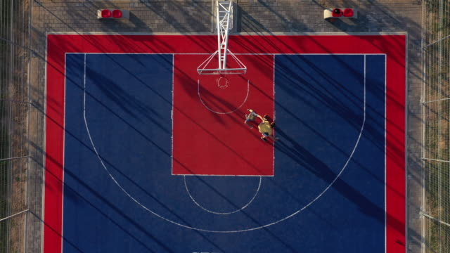 vídeos de stock e filmes b-roll de aerial view of two basketball player on basketball court - pátio