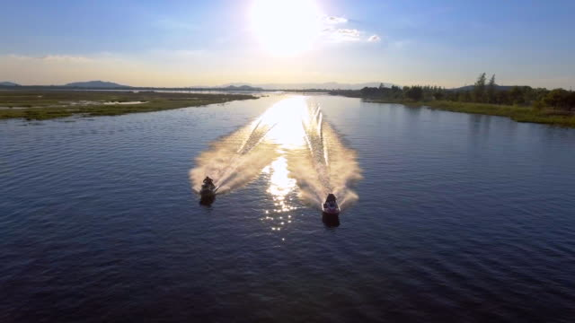 aerial view of two jet boat racing in the lake at sunset - jet ski stock videos & royalty-free footage