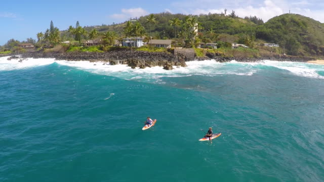 Aerial view of two men sup stand-up paddleboard surfing in Hawaii.