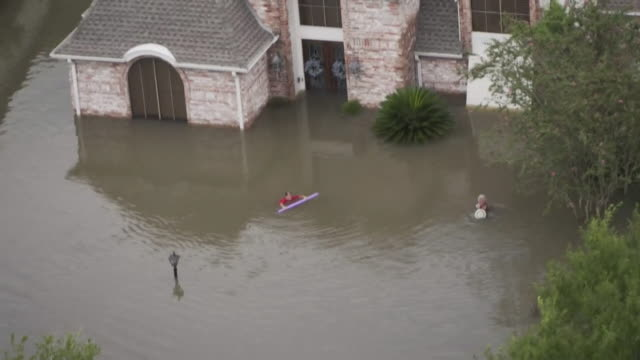 aerial view of two people being rescued by boat from flooded streets in houston - salvataggio video stock e b–roll