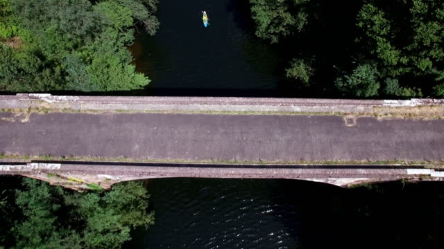 Aerial view of two people canoeing under a bridge on the Lot river, Aveyron, France