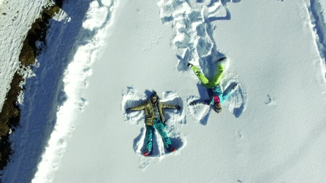aerial view of two people making a snow angel, - lying on back stock videos and b-roll footage