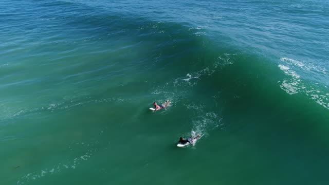 vídeos y material grabado en eventos de stock de vista aérea de dos surfistas en el mar - gold coast