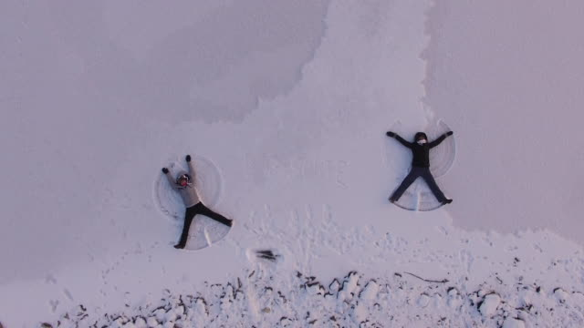 aerial view of two women making a snow angel, lapland, finland - angel点の映像素材/bロール