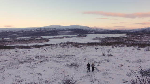Aerial view of two women walking on a frozen landscape, Lapland, Finland