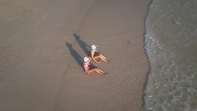 Aerial view of two young woman sunbathing on beach