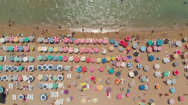 aerial view of umbrellas in a beach of aegean sea - beach umbrella stock videos and b-roll footage