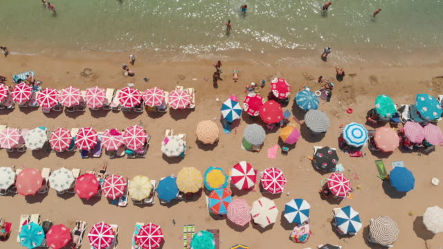 vídeos de stock e filmes b-roll de aerial view of umbrellas in a beach of aegean sea - chapéu