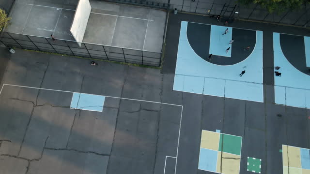 aerial view of unrecognizable people playing basketball at a city park in brooklyn - public park stock videos & royalty-free footage